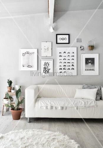 Sofa unter Bildergalerie im monochromen Wohnzimmer