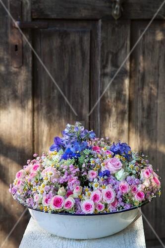 Old washbasin full of flowers in front of wooden door