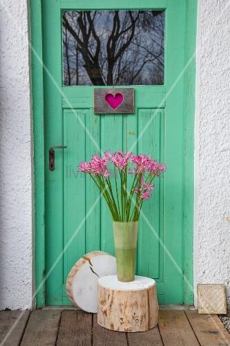 Vase of pink nerines on slice of tree trunk against front door