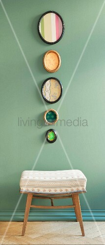 Biedermeier fabric patterns in oval photo frames hanging on a pastel-green wall above an upholstered stool