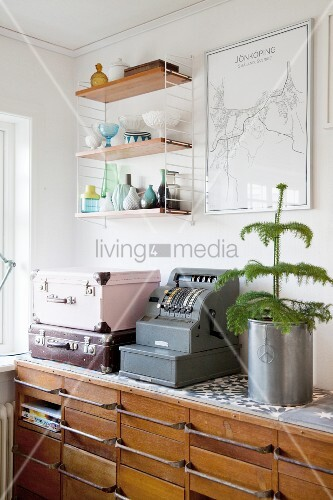 Retro cash register and suitcases on top of chest of drawers below String shelves