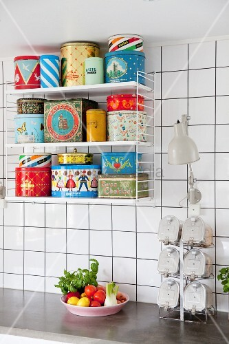 Various colourful retro tins on String shelves in whit-tiled kitchen