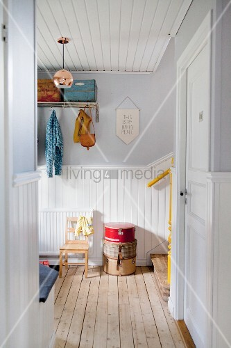 Wooden ceiling and foot of staircase in white, wood-clad, Scandinavian hallway with retro ambiance