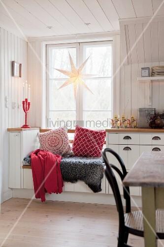 Fur blanket and cushions on window seat below star decoration in kitchen window