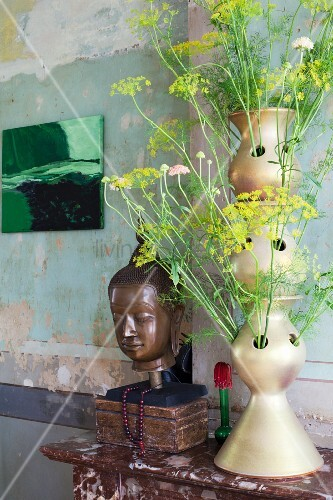 Fennel flowers in artistic vase next to head of Buddha in vintage interior