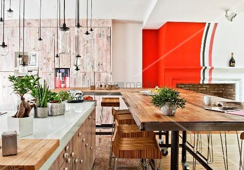 Kücheninsel mit weisser Arbeitsfläche, Pendelleuchten aus Gläsern und langer Esstisch mit Barhockern in offenem Wohnraum