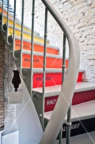 Wendeltreppe mit bunten Fronten im Treppenraum mit Sichtmauerwerk