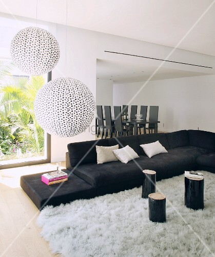 Spherical lamps above black sofa and view of dining table