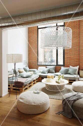 Furniture made from wooden pallets and brick wall in elegant lounge of loft apartment