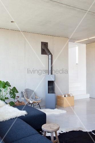 Polstercouch, Zimmerpflanze und Kamin in offenem Wohnraum mit Betonwand
