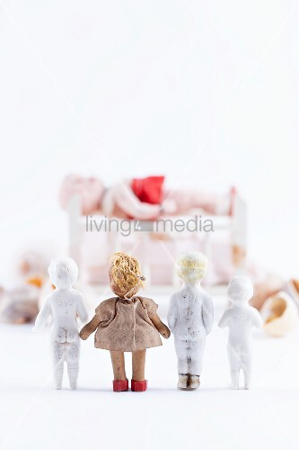Small dolls stood up looking towards large doll on bed