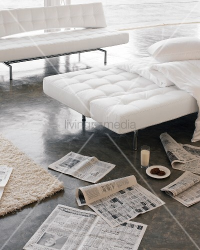 White folding sofas and newspapers scattered on concrete floor