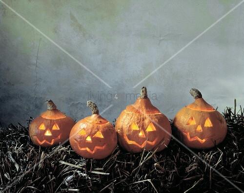 Vier leuchtende Halloweenkürbisse auf Strohballen
