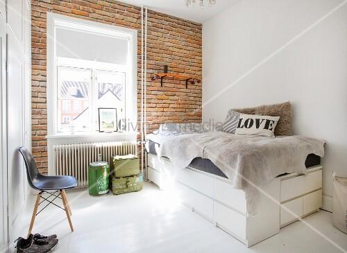 Selbstgebautes Bett auf weißen Kommoden vor einer Backsteinwand