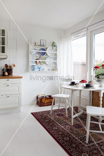 Dining table on Oriental rug in white country-house kitchen