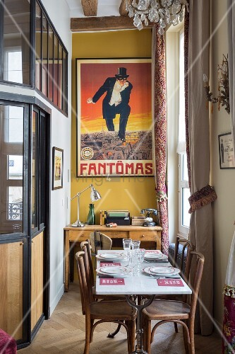Narrow dining area with desk below retro poster on mustard-yellow wall