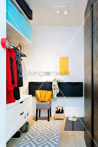 Eingebaute Dielenmöbel mit Stauraum und Aufbewahrungsboxen, gelbes Revisionstürchen an weißer Wand