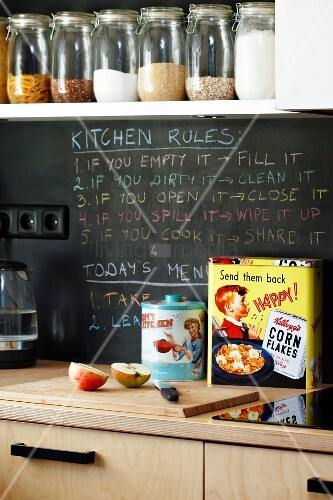 Storage jars on white kitchen shelf above writing on chalkboard splashback and retro tins