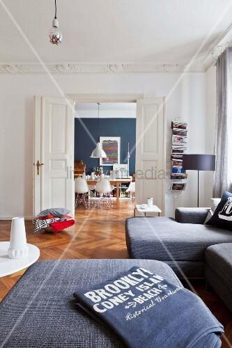 Herringbone parquet floor, stucco frieze and double doors in living area of renovated period apartment