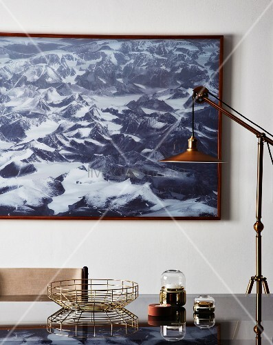 Standard lamp and ornaments on glass table in front of picture of mountains