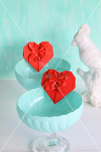 Red origami hearts in turquoise dessert bowls next to china bird