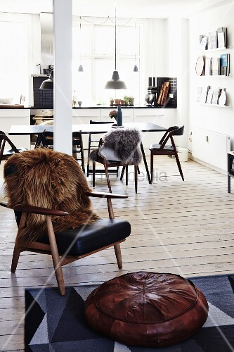 Brown fur blanket on retro armchair and pouffe in open-plan living room