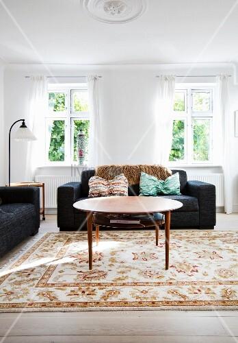 Runder Couchtisch Und Schwarzes Sofa Im Hellen Wohnzimmer