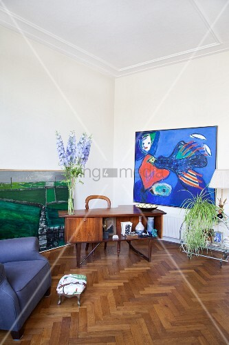 Retro desk and modern painting in living area with oak parquet floor