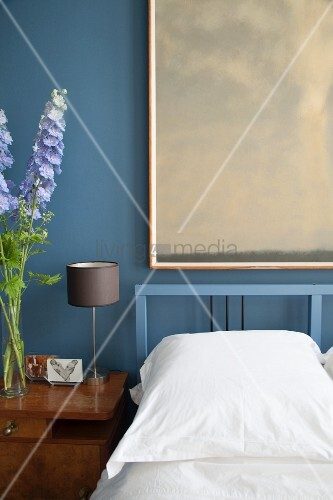 Framed picture on blue bedroom wall and flowers on bedside cabinet