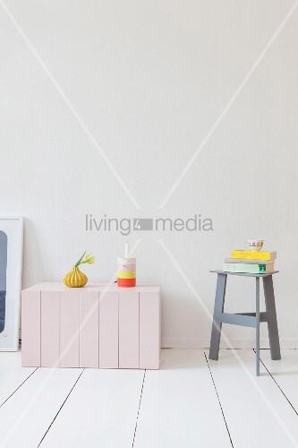 Rosa Holztruhe und grauer Hocker mit Bücherstapel auf weißem Dielenboden