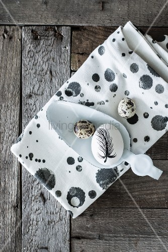 Egg painted with feather and quail eggs on spotted cloth