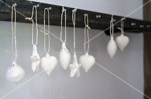 Christmas-tree baubles dipped in plaster and hung from hooks on wall