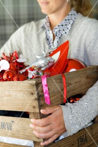 Frau trägt Holzkiste mit rotem Weihnachtsschmuck