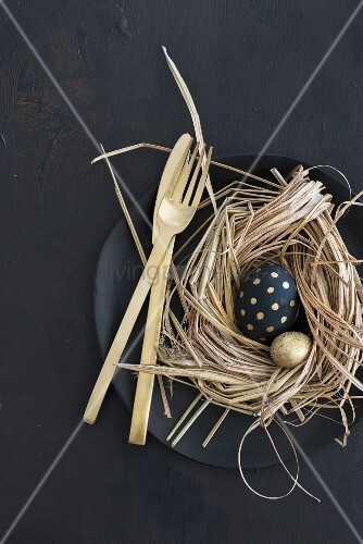 Easter arrangement of gold and black eggs in nest and gold cutlery on black plate