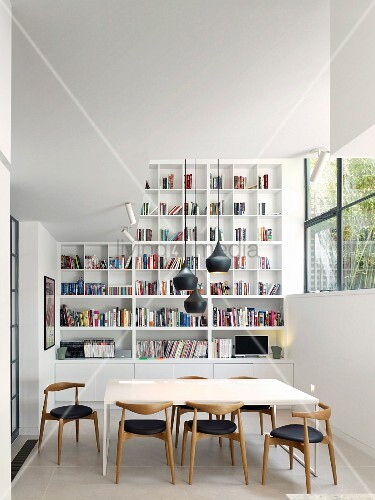 Bookcases and retro chairs in modern dining room with high ceiling
