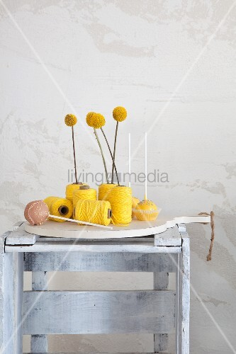 Craspedia arranged in reels of yellow thread next to cake pops