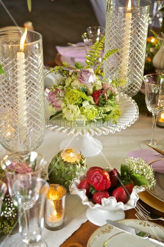 Flowers and candle lantern on festively set table