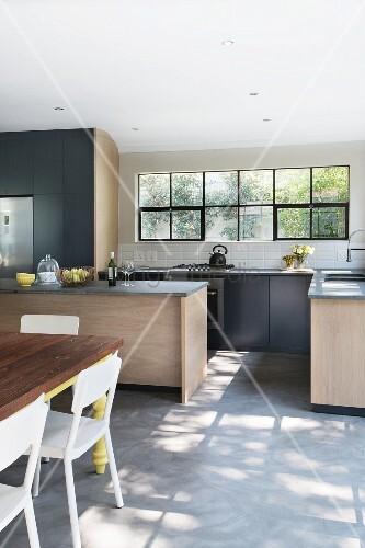 moderne k che mit essplatz licht f llt durch sprossenfenster auf betonboden bild kaufen. Black Bedroom Furniture Sets. Home Design Ideas