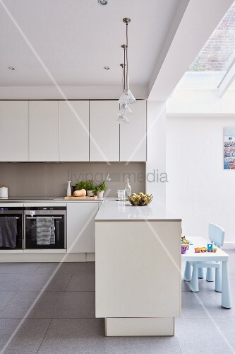 White fitted kitchen, base unit as partition and children's furniture below skylight