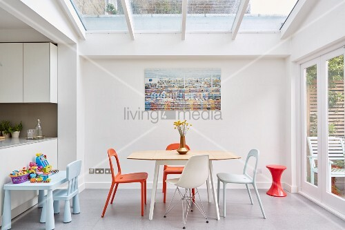 Bright dining area below skylight in extension to period building with French windows