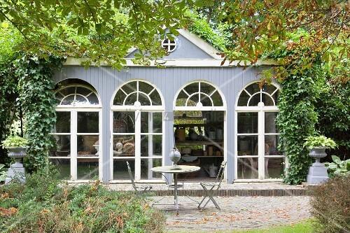 Terrasse vor einer Orangerie mit Bogenfenstern