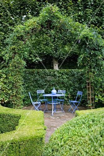 Sitzplatz mit blauen Gartenmöbeln unterm bewachsenen Pavillon