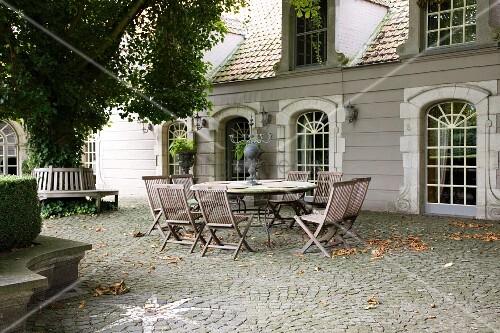 Sitzplatz auf dem gepflasterten Hof vor klassischem Gebäude