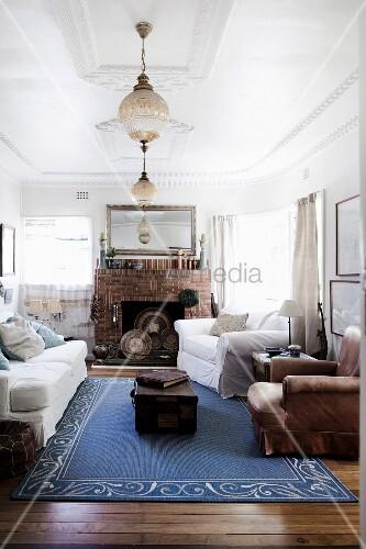 Blauer Teppich im Wohnzimmer mit Stuckdecke und offenem Kamin – Bild ...
