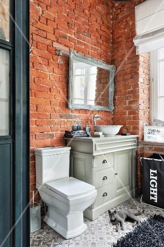 Vintage-style furnishings and brick walls in bathroom