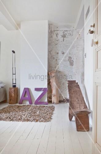 Schlafzimmer mit Leder-Teppich, lila Deko-Buchstaben und Ethno ...