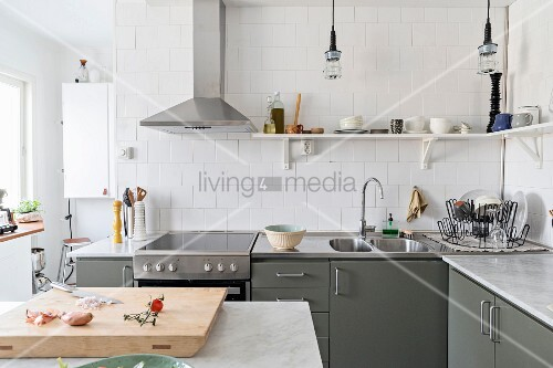 Stainless steel extractor hood and shelves mounted on white-tiled walls in grey fitted kitchen