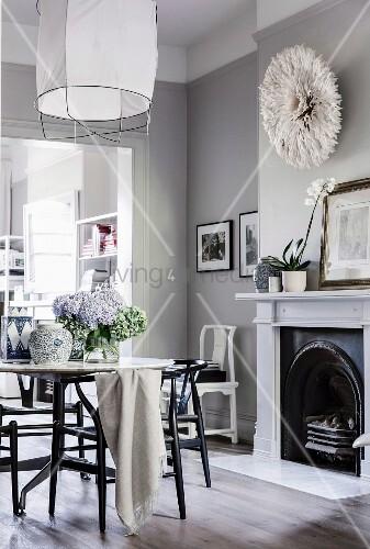 Esstisch vor dem offenen Kamin im eleganten Wohnraum
