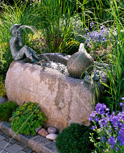 Stone trough with ball and flute player as a water feature
