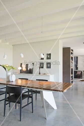 Offener Wohnraum mit modernem Esstisch und Estrichboden